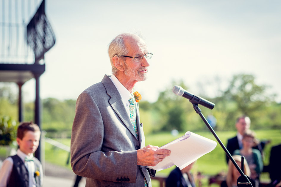bride's father giving a speech outdoors