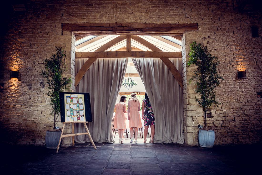 bridesmaids look at room set up for wedding breakfast at Cripps Barn