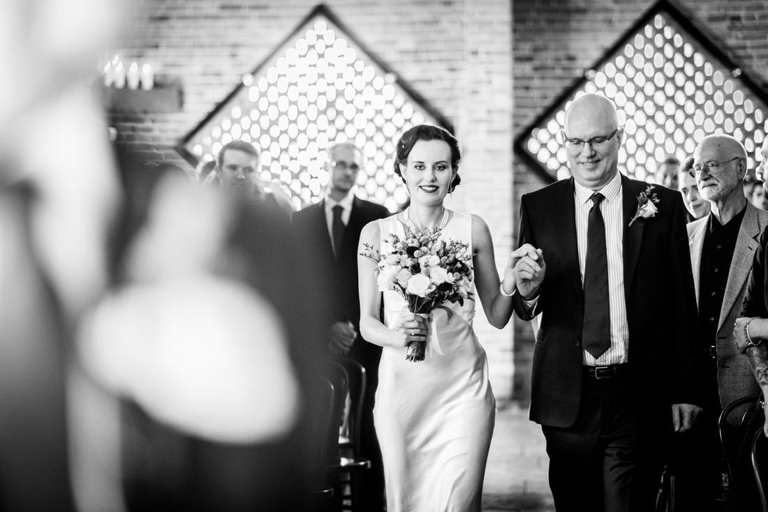 bride walks down the aisle at Shustoke Farm Barns wedding