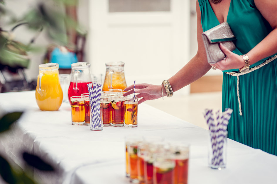 guest takes glass of Pimms at wedding