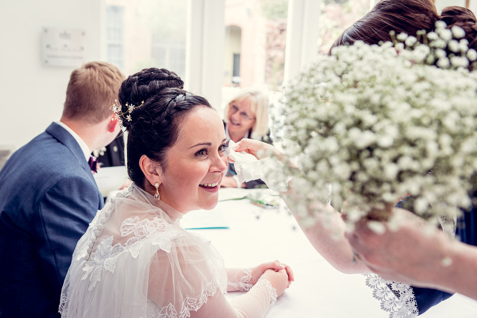 bridemaid wipes tears from bride's eyes