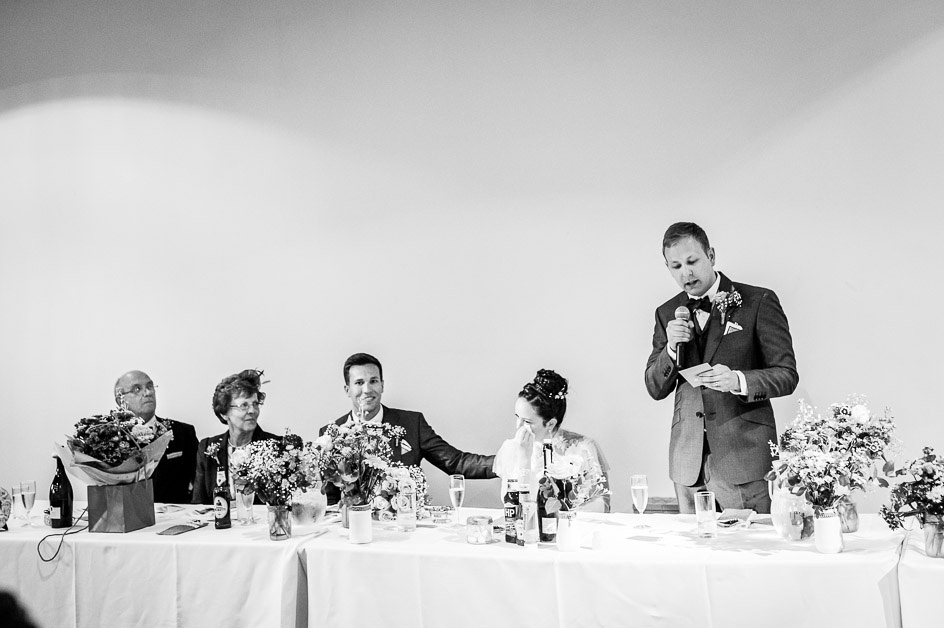 bride wipes a tear from  her eye during groom's speech