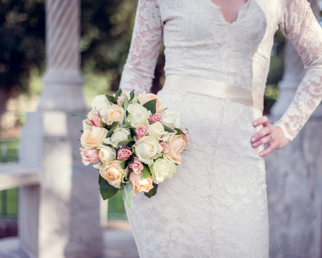 bride in lace dress holding bouquet of cream, peach and pink roses