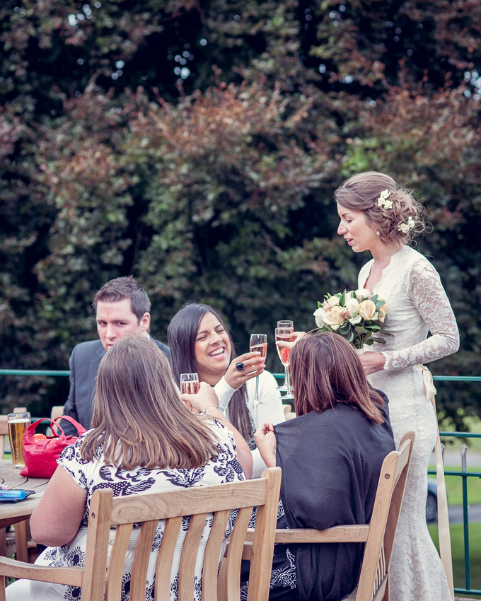 bride in lace dress drinking pink champagne