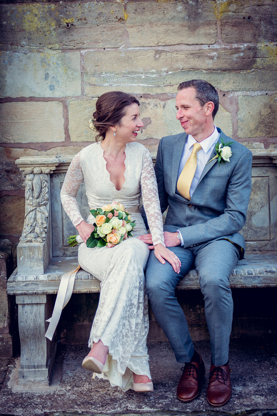 bride and groom sitting on bench at Weston Hall