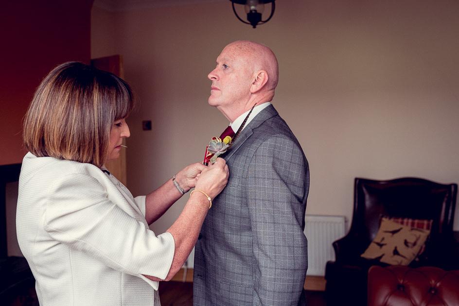Bride's mum pins buttonhole onto emotional dad