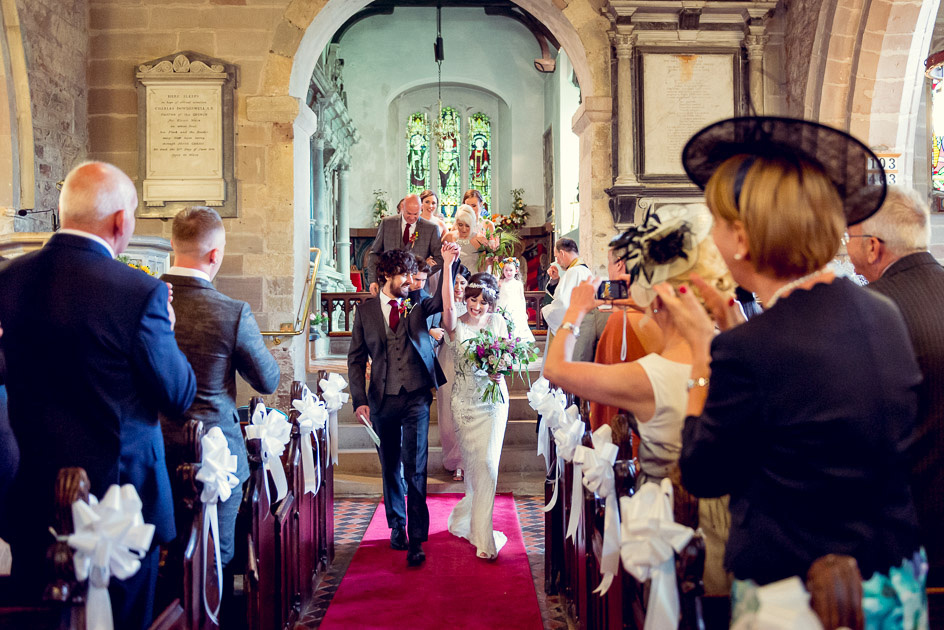 Jubilant bride and groom exit St Leonard's Church in Beoley
