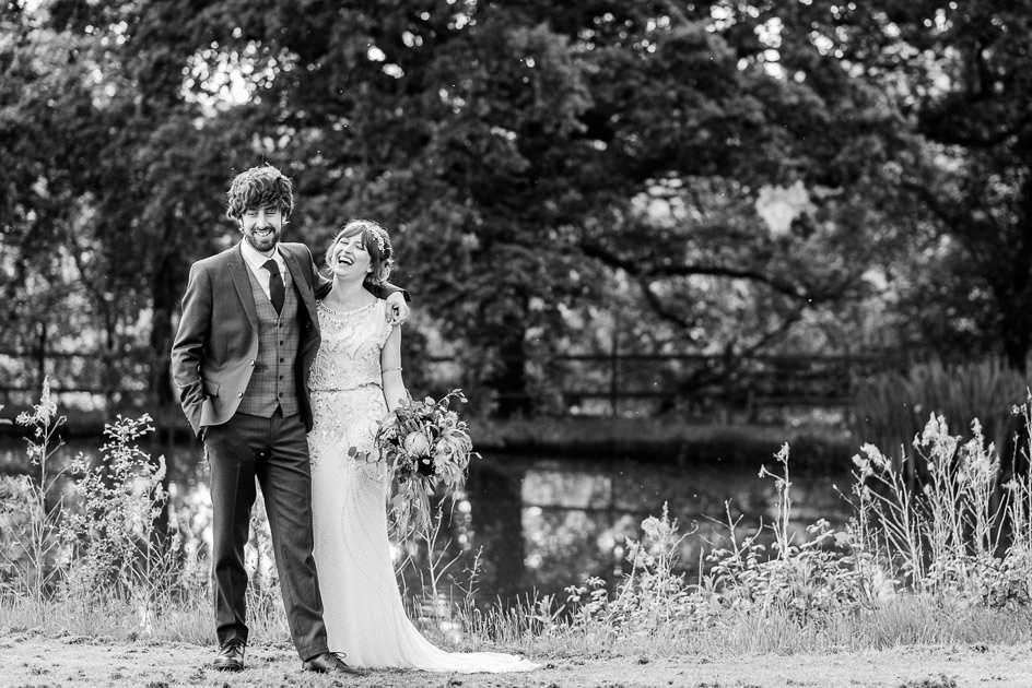 bride and groom laugh by lake at Gorcott Hall
