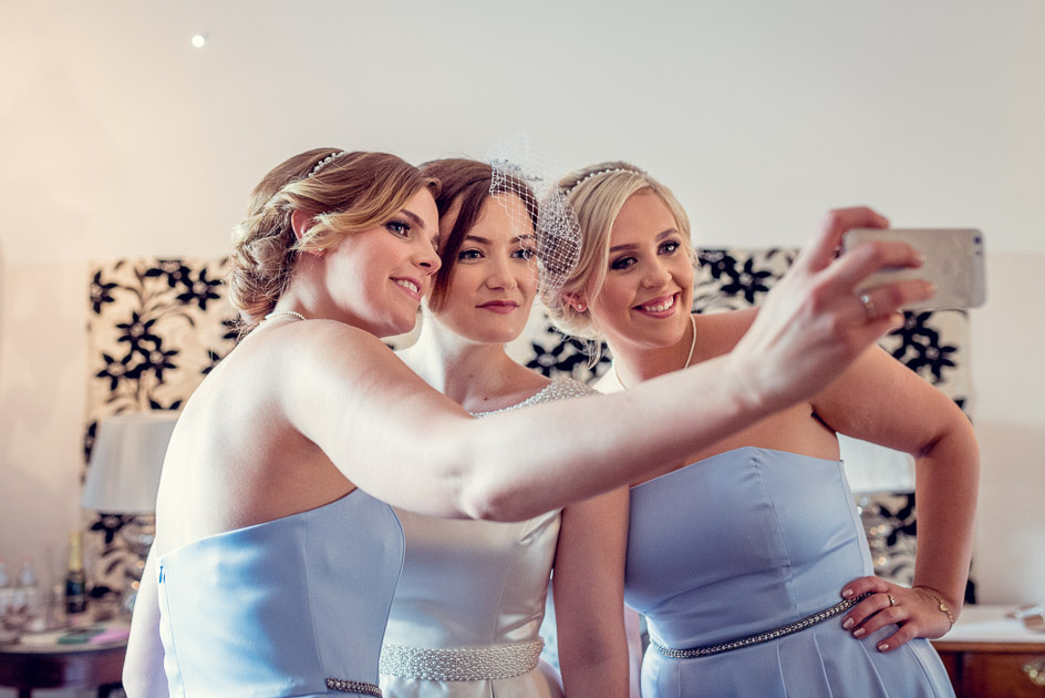 bride and bridesmaids take selfie