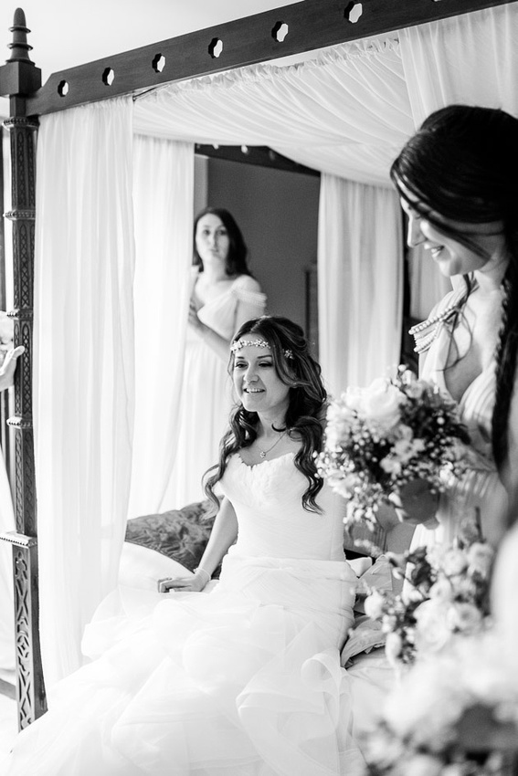 bride sits on four poster bed surrounded by bridesmaids before wedding at Old Thorns