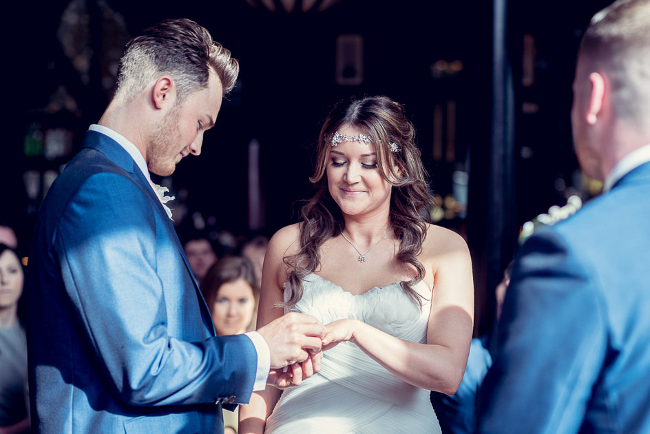bride and groom exchange rings at Old Thorns wedding