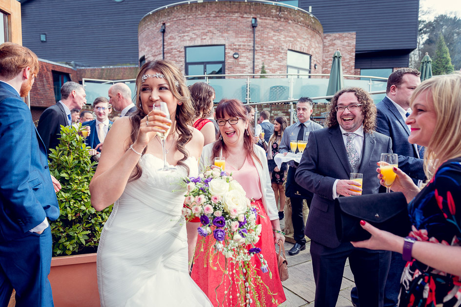 guests laughing with bride at drinks reception at Old Thorns