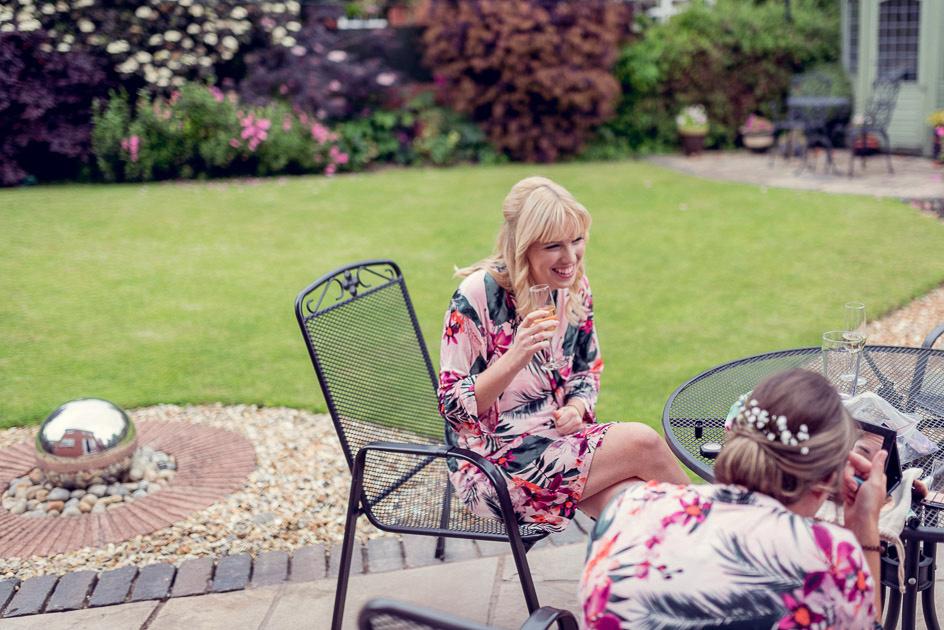 bride drinking prosecco getting ready in garden