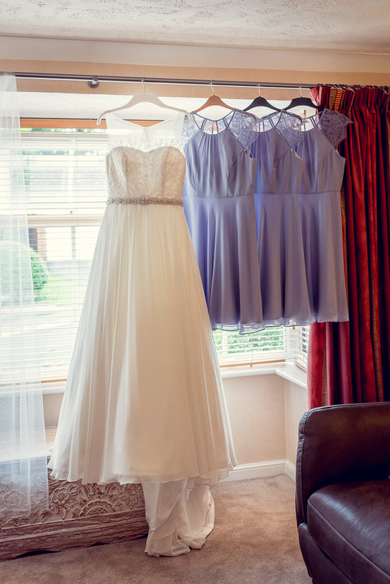bride and lilac bridesmaids dresses hanging up