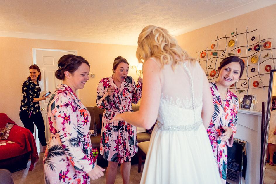 bridesmaids look at bride in dress