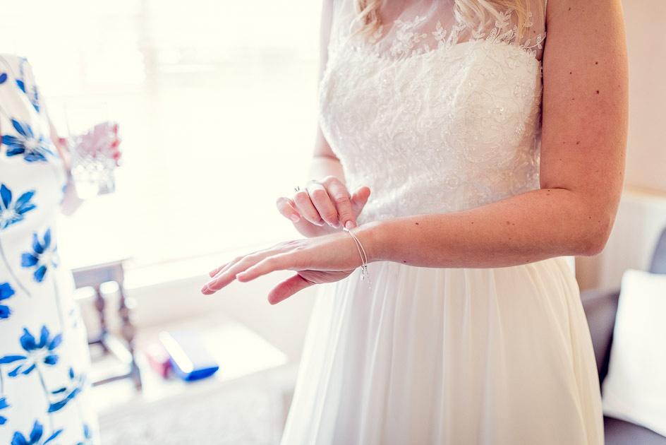 bride looks at bracelet