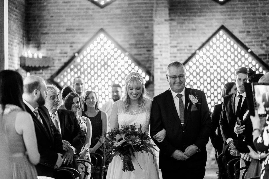 bride walks down the aisle at Shustoke Farm Barns in Warwickshire