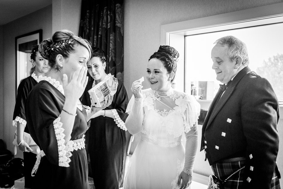 bride and bridesmaid crying with dad before wedding