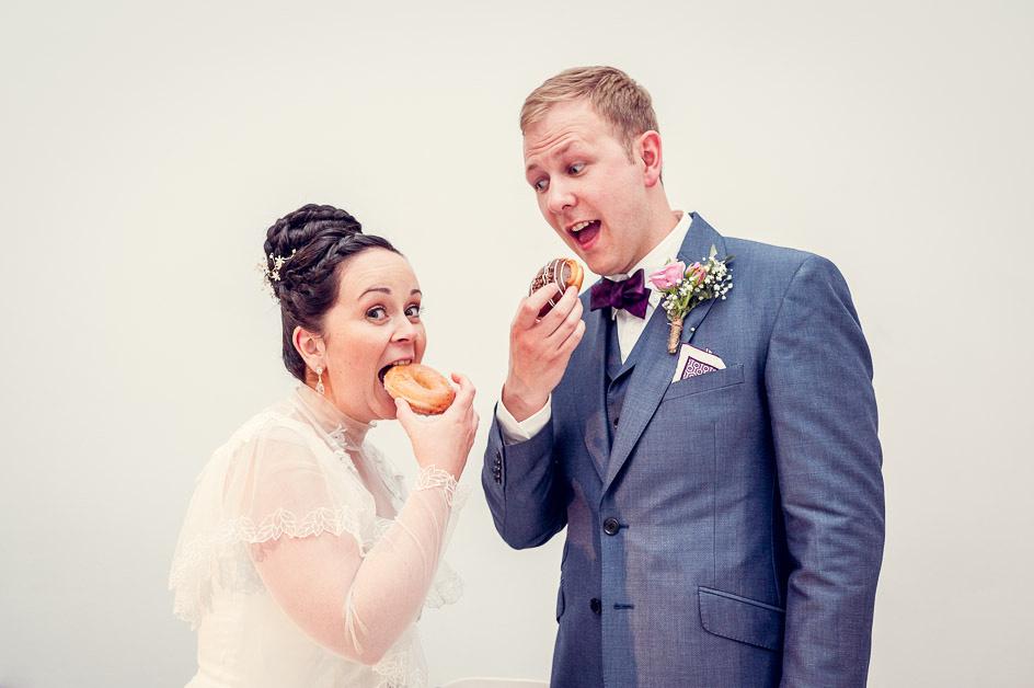 bride and groom eat doughnuts