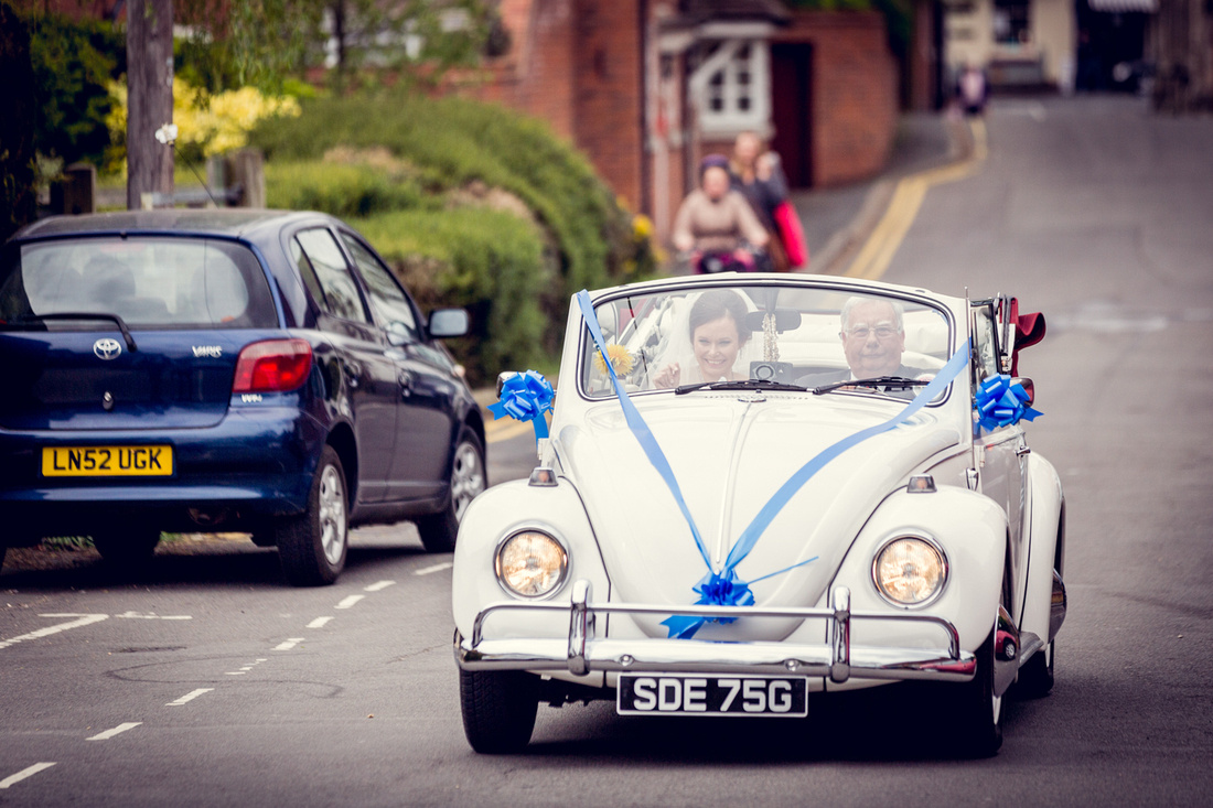 bride arrives in vintage VW convertible beetle for Warwickshire wedding