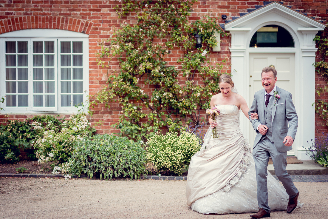 Wedding Photography at Wethele Manor in Warwickshire summer outdoor ceremony relaxed creative female photographer bride walking with dad