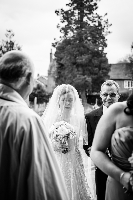bride composes herself outside church in Henley  in Arden