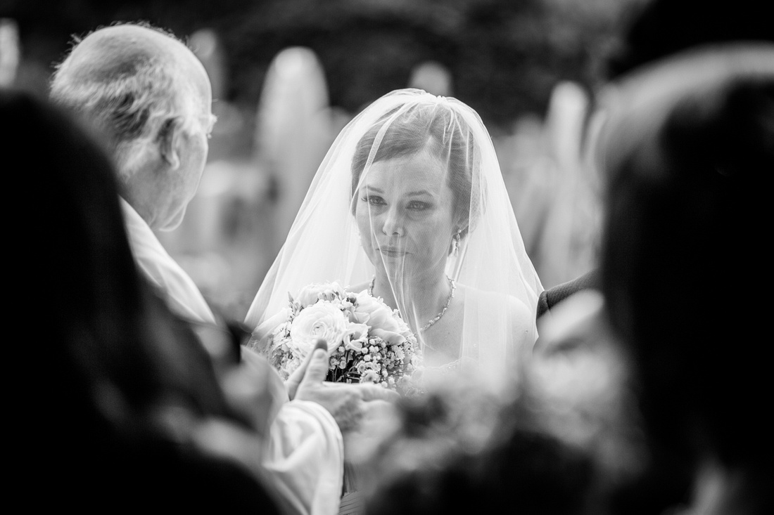 bride under veil waiting outside church in Henley in Arden