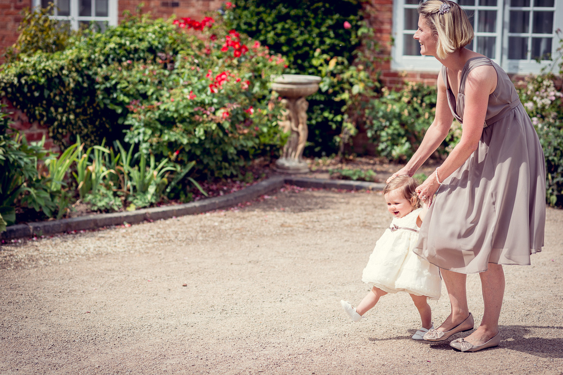 Wedding Photography at Wethele Manor in Warwickshire summer outdoor ceremony relaxed creative female photographer flowergirl toddler bridesmaid walking