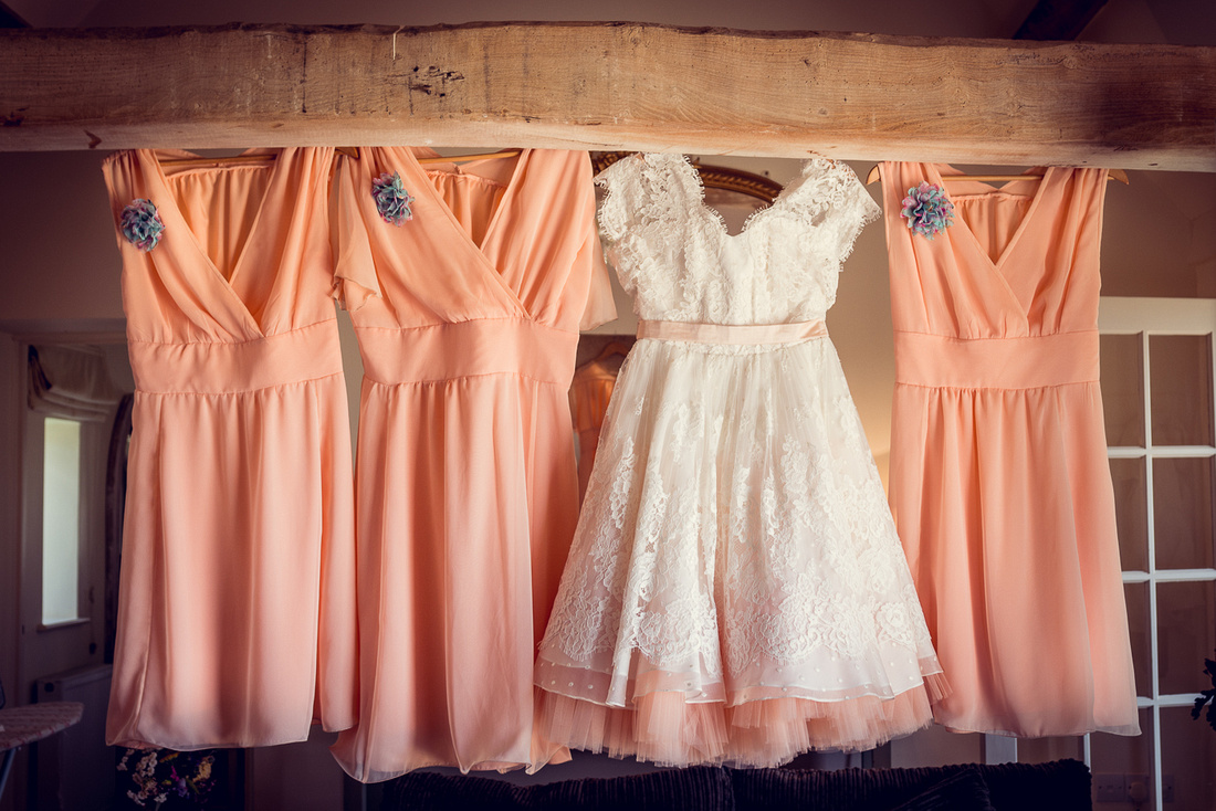 vintage style peach Couture Company wedding dress with lace and bridesmaids dresses hanging in a barn