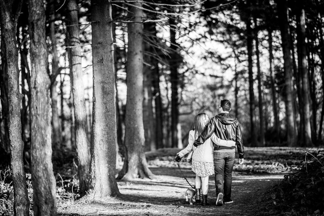 happy couple walk through the tree in the Lickey Hills with their puppy