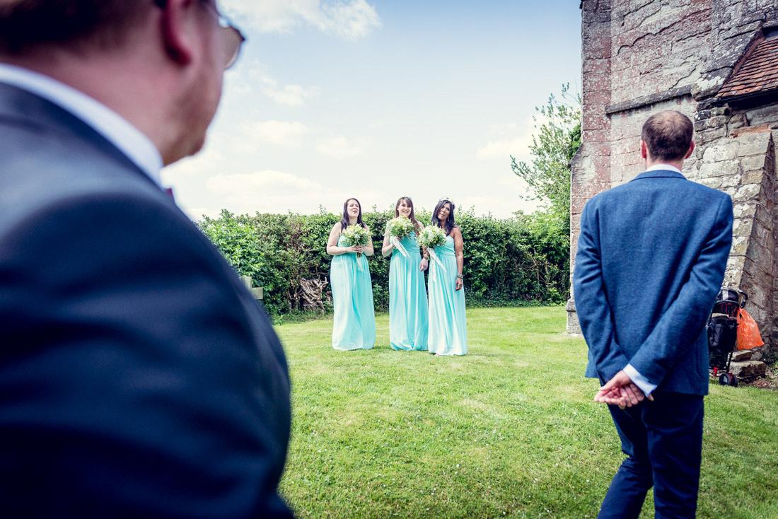 bridesmaids watch groom entering St Mary's Church Hatton Warwickshire wedding
