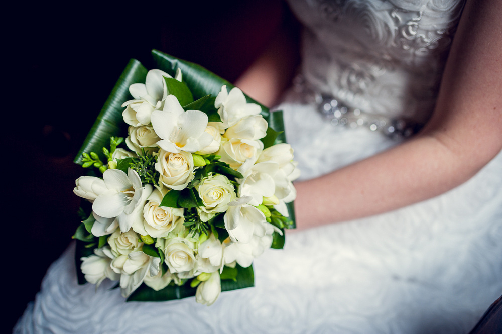 bride's bouquet of cream roses and freesias with aspidistra leaves