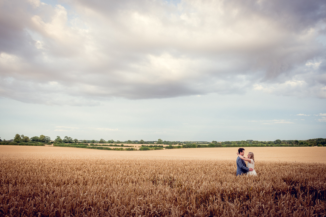 bride and groom in cornfield at Cripps Barn in Bibury