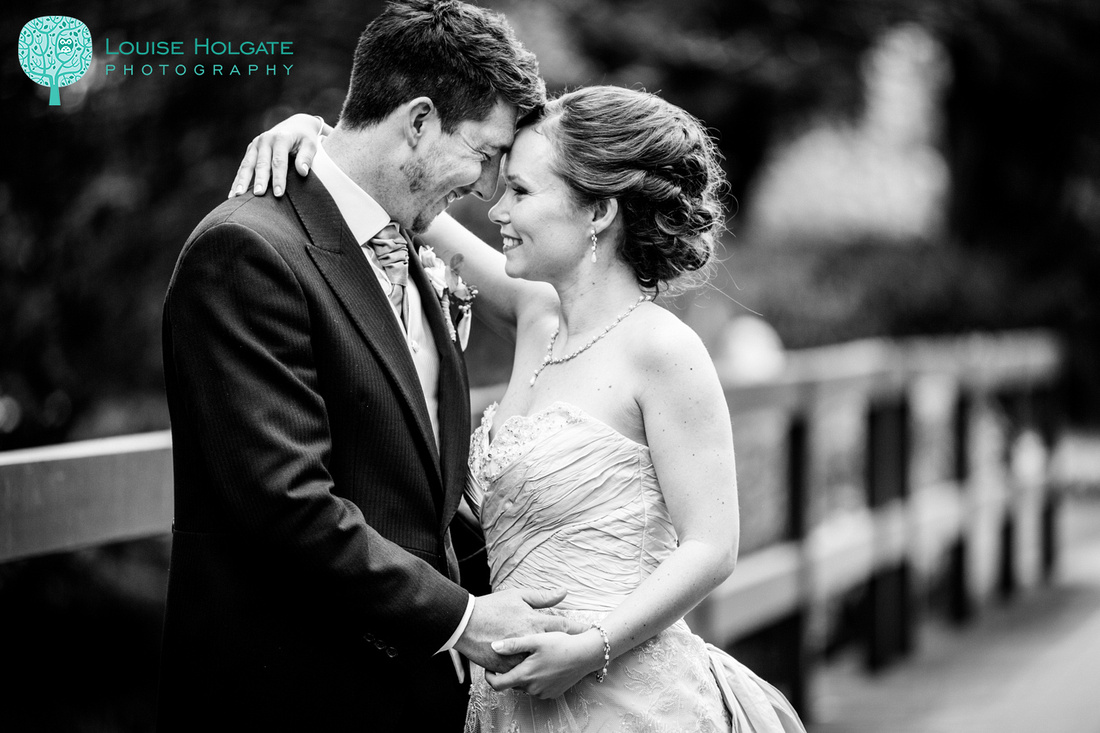 romantic portrait of bride and groom on bridge at Ardencote Manor