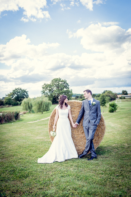 wedding photography at wootton park in warwickshire bride and groom by hay bale