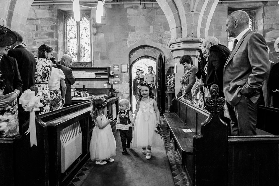 Bridesmaids and pageboys walk into St Leonard's Church Beoley