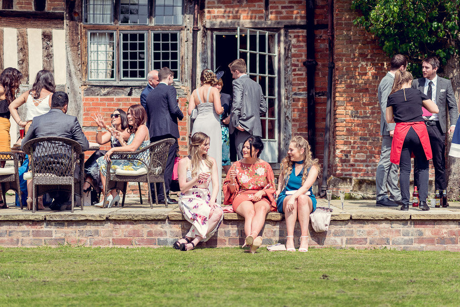wedding guests relax in sunshine at Gorcott Hall