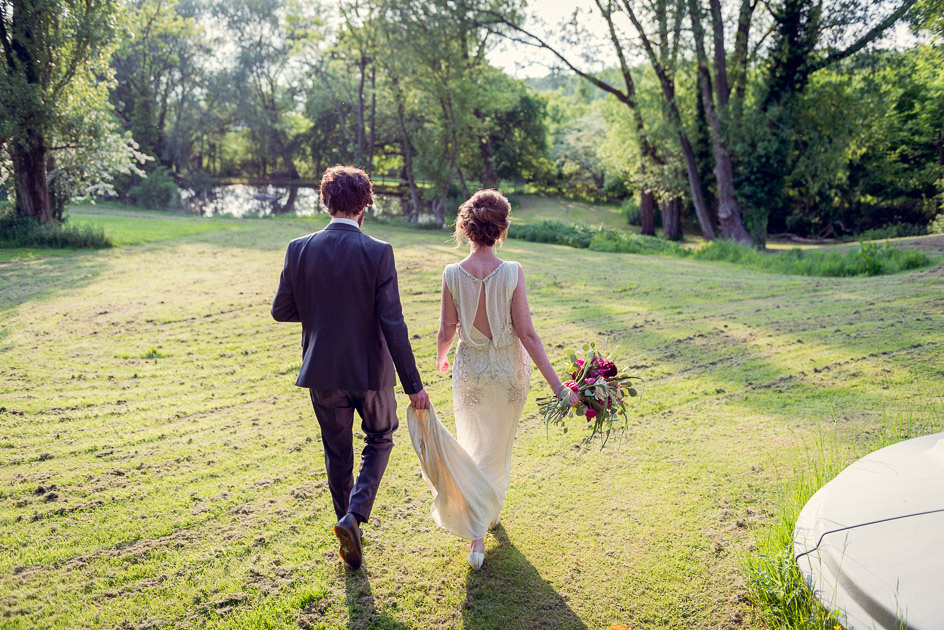 bride and groom walk to lake at Gorcott Hall in evening sun