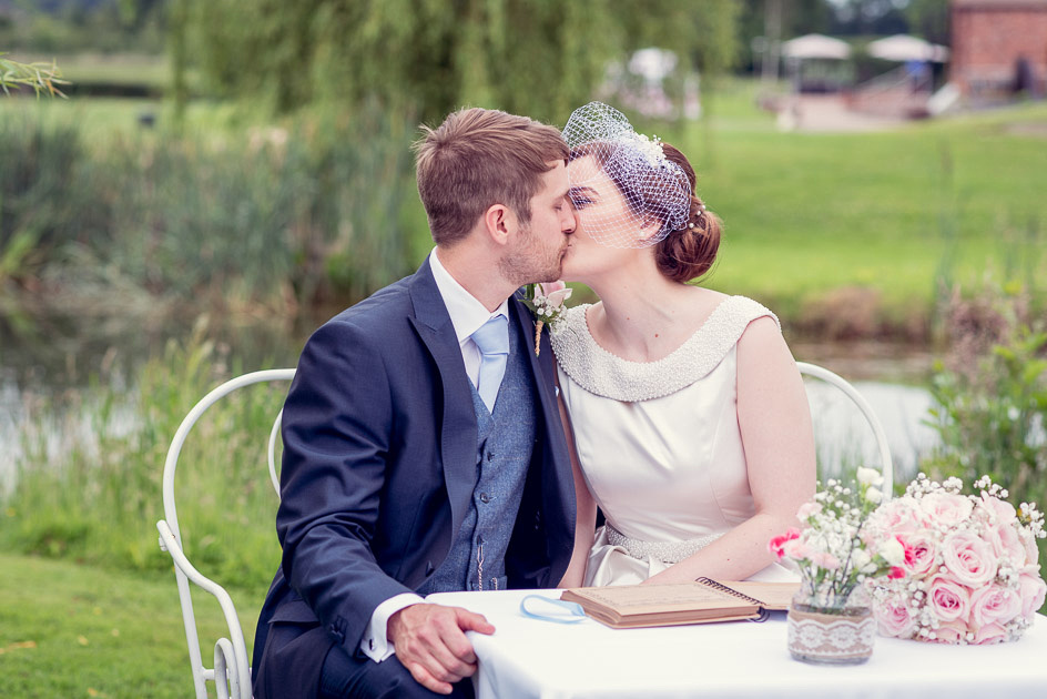 bride and groom kiss after outdoor wedding ceremony at Wootton Park