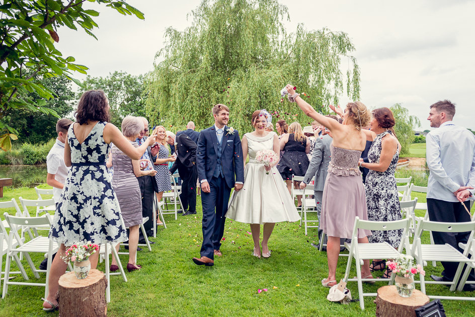 guests throw confetti as bride and groom walk down the aisle at Wootton Park