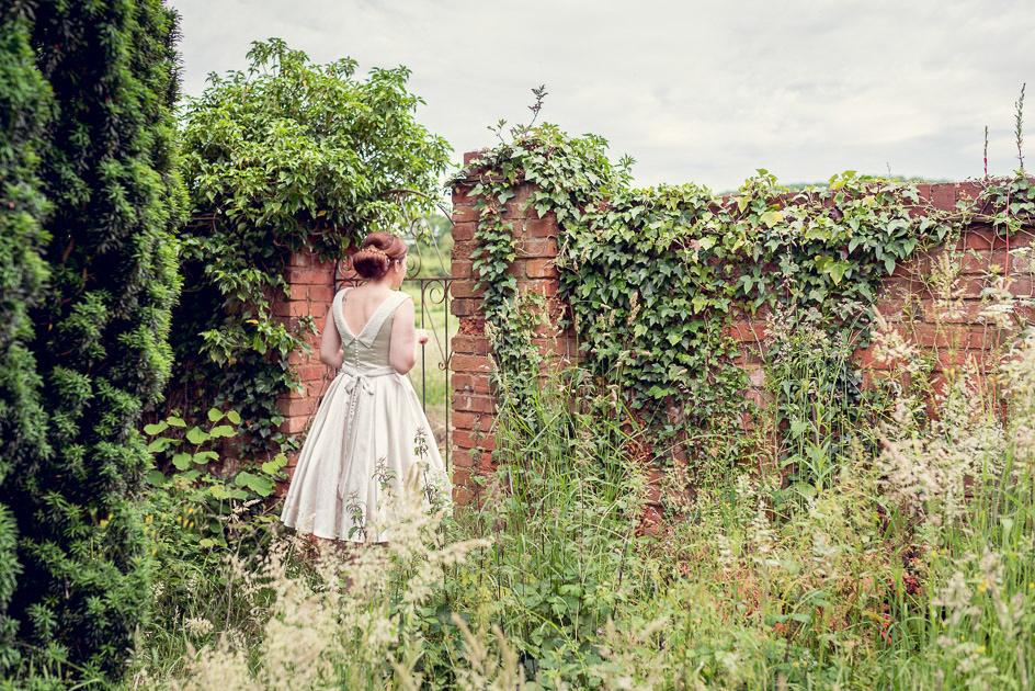 bride in vintage dress looks through gate in overgrown garden