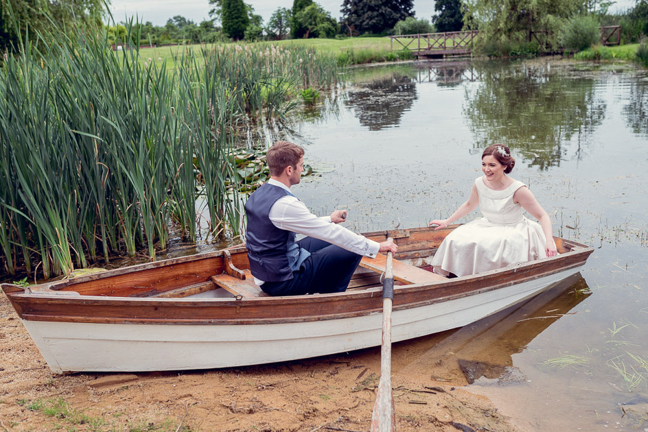 bride and groom in rowing boat at Wootton Park