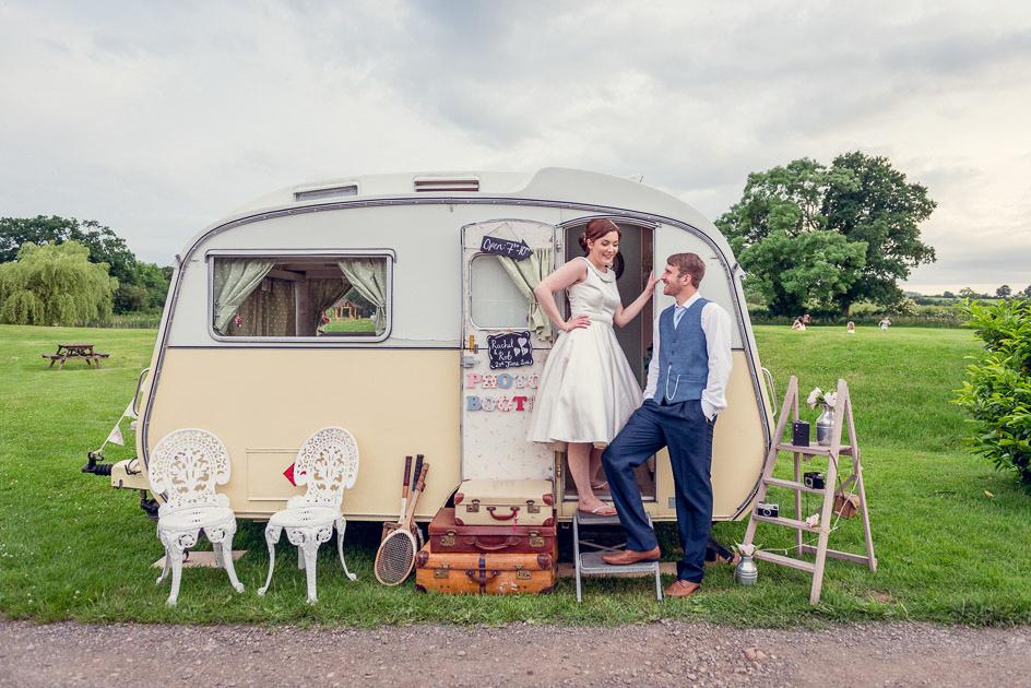 bride and groom with vintage caravan photobooth