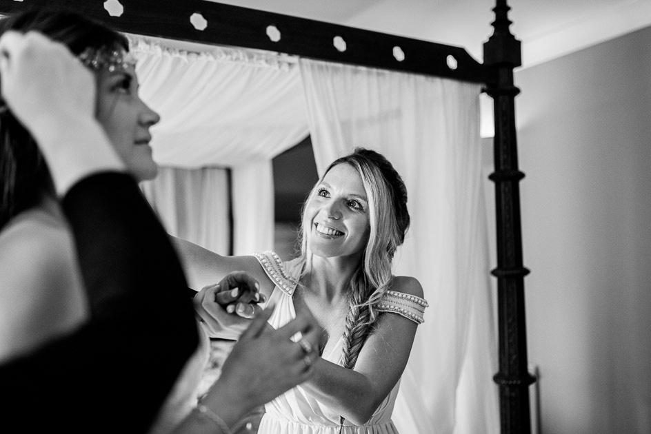 smiling bridesmaid helps bride with diamante headband