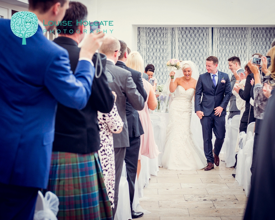 bride punches air as she walks down the aisle