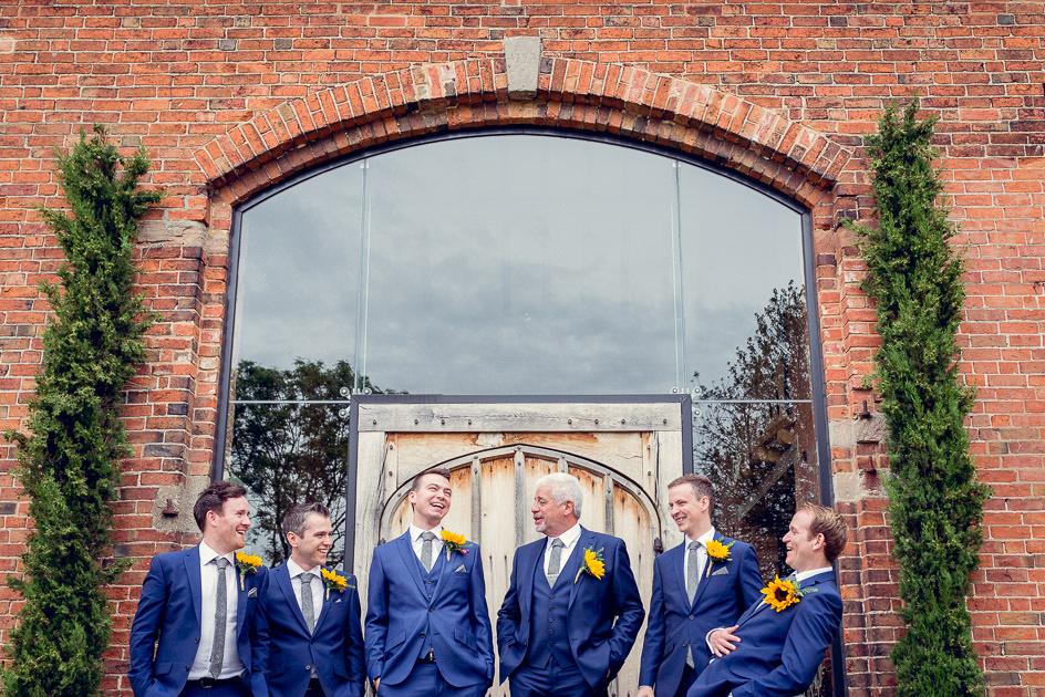 groom laughing with groomsmen before wedding at Shustoke Farm Barns