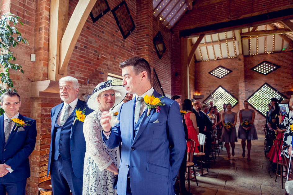 nervous groom waits for bride at Shustoke Farm Barns in Warwickshire