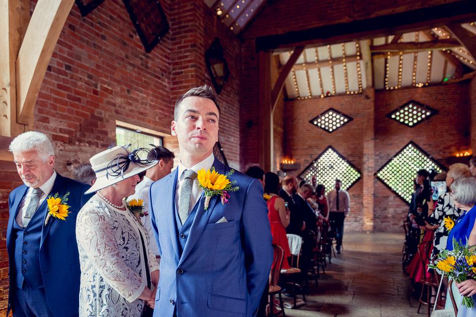 groom waits for bride at Shustoke Farm Barns in Warwickshire