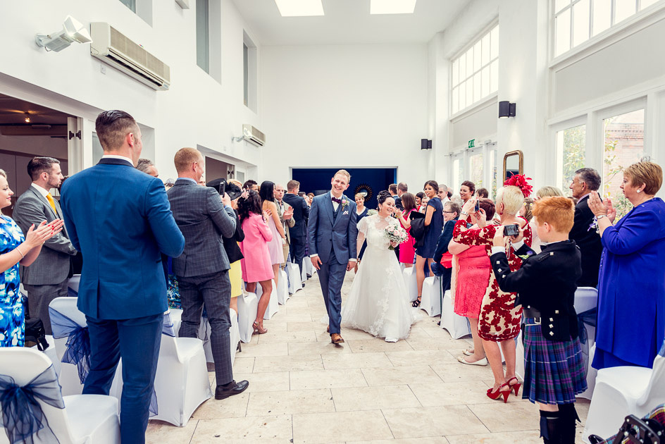 happy bride and groom walk down the aisle at Fazeley Studios