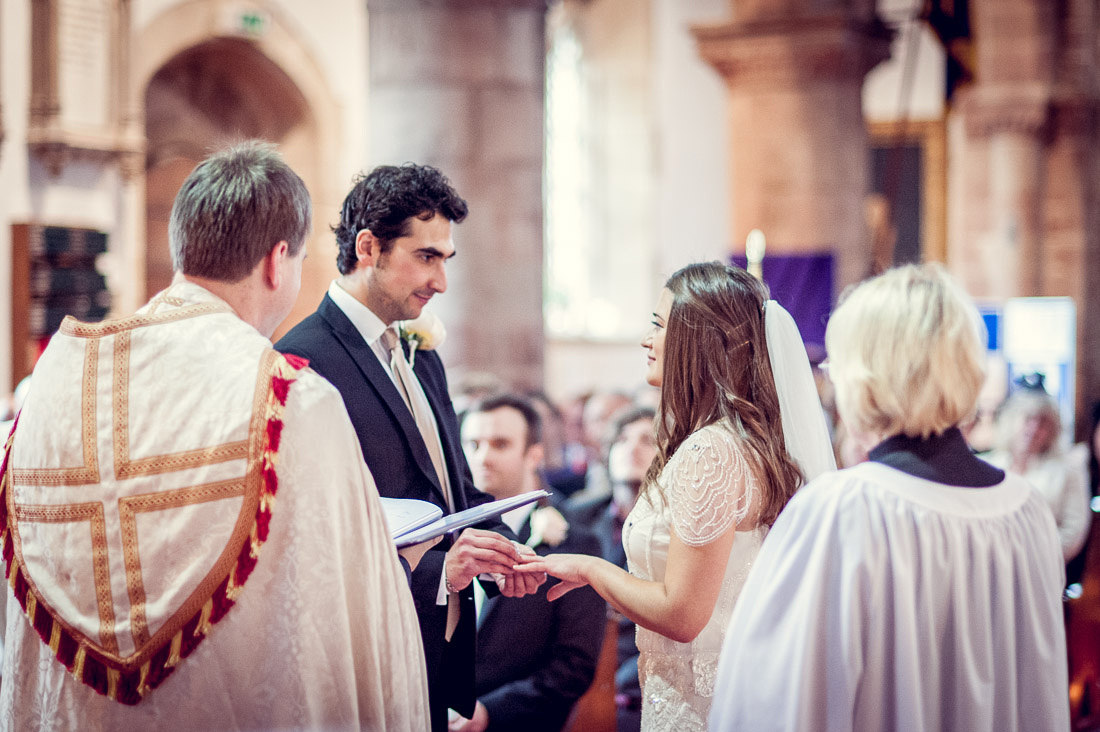 bride and groom exchange rings at St Mary and St Bartholomew Church in Hampton in Arden